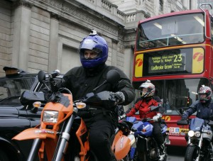 3 motorcyclists with bus and taxi in London